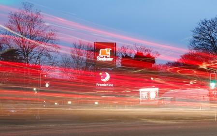 FILE PHOTO: Cars leave light trails as they pass a Premier Inn hotel in Liverpool