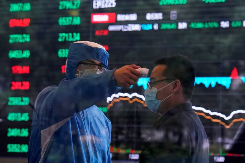 FILE PHOTO: A worker wearing a protective suit takes body temperature measurement of a man inside the Shanghai Stock Exchange building, as the country is hit by a new coronavirus outbreak, at the Pudong financial district in Shanghai