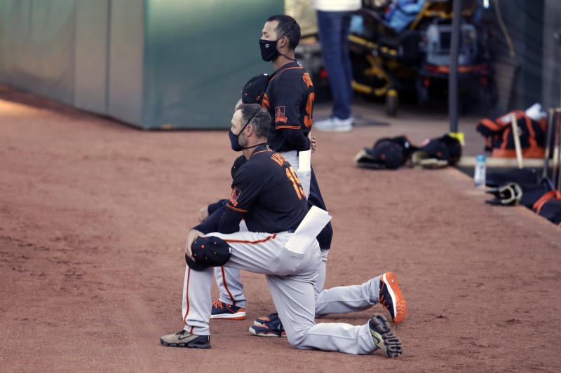 San Francisco Giants manager Gabe Kapler kneels during the national anthem prior to an exhibition baseball game against the Oakland Athletics on Monday in Oakland, California. (AP Photo/Ben Margot)