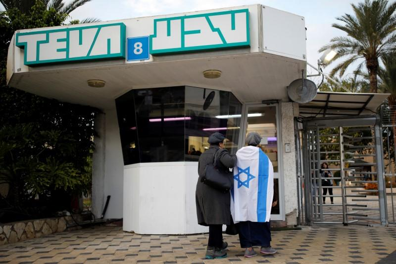 2090adae7 FILE PHOTO  Workers of Teva Pharmaceutical Industries stand at the entrance  to their facility in