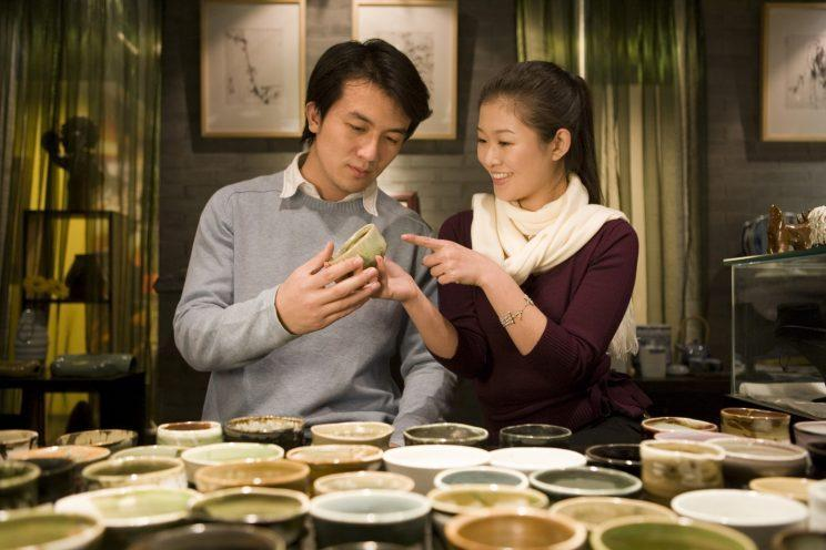 A young couple looks at a variety of handmade pottery on display. (Photo: Getty Images)