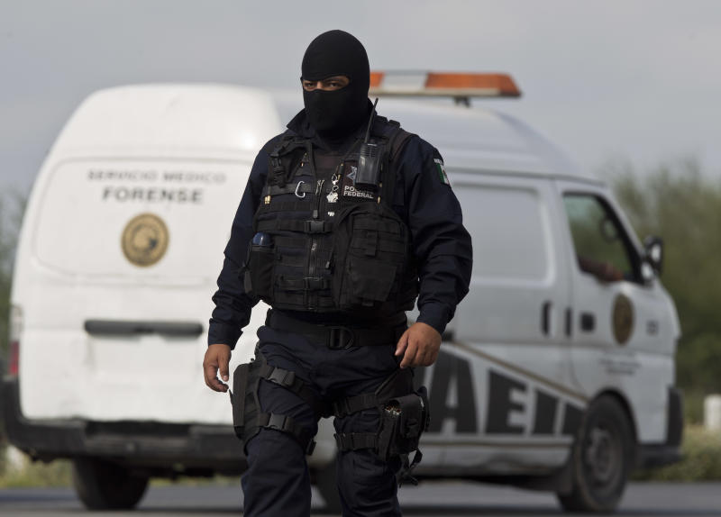 A federal policeman guards the area where dozens of bodies, some of them mutilated, were found on a highway connecting the northern Mexican metropolis of Monterrey to the U.S. border found in the town of San Juan near the city of Monterrey, Mexico, Sunday, May 13, 2012. (AP Photo/Christian Palma)