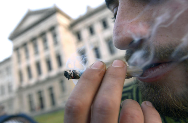A man smokes marijuana outside the Congress where lawmakers debate a bill to legalize marijuana and regulate production and distribution in Montevideo, Uruguay, Wednesday, July 31, 2013. Uruguay's unprecedented proposal to fight organized crime by creating a legal, government-licensed marijuana market was fiercely debated by lawmakers Wednesday, as the governing coalition counted every vote in hopes of winning passage in the lower house of Congress. (AP Photo/Matilde Campodonico)