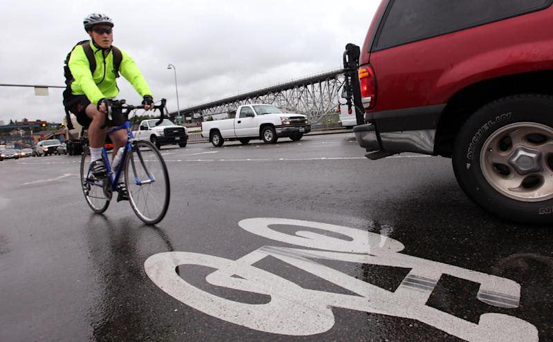 FILE - This May 31, 2012 file photo shows a bicyclist commuting during rush hour past a logo designating a bike route in Seattle. Americans are a mistrustful bunch. Nearly two-thirds say you can't be too careful in dealing with people, according to the General Social Survey, a massive survey of Americans conducted regularly since 1972 with funding from the National Science Foundation. The poll found that 75 percent mistrust people driving cars while they're driving, biking or walking. (AP Photo/Elaine Thompson, File)