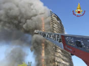 Smoke billows from a building on fire in Milan, Italy, Sunday, Aug. 29, 2021. Firefighters were battling a blaze on Sunday that spread rapidly through a recently restructured 60-meter-high, 16-story residential building in Milan. There were no immediate reports of injuries or deaths. (Vigili del Fuoco via AP)