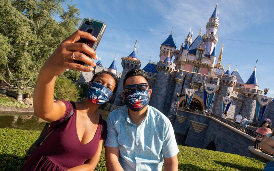 Guests in masks pose in front of Sleeping Beauty's castle at Disneyland Resort California - Handout/Getty Images
