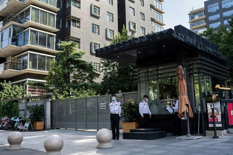 Security guards stand at the main gate to a luxury apartment building in Beijing where two flats were seized from Hong Kong-born actor Jackie Chan in an ownership row