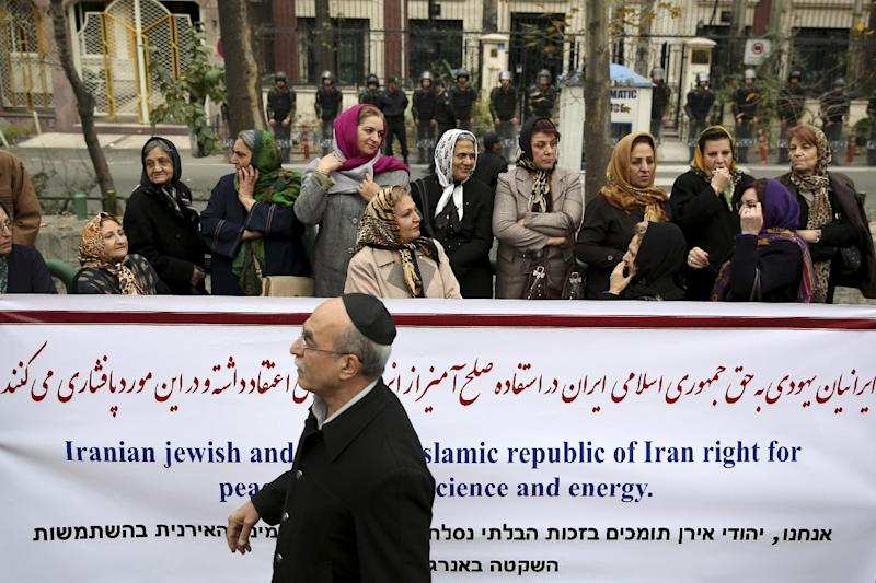 An Iranian Jewish man walks past a banner during a gathering of Iran's Jewish community Iranian Jews hold a banner during a gathering of Iran's Jewish community outside a U.N. office in Tehran, Iran, Tuesday, Nov. 19, 2013. Hundreds of Iranians including university students and members of the country's Jewish community rallied Tuesday in support of the Islamic Republic's disputed nuclear program on the eve of the resumption of talks with world powers. (AP Photo/Ebrahim Noroozi)