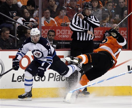 Philadelphia Flyers Brayden Schenn, right, goes down hard after a check from Winnipeg Jets Grant Clitsome in the second period of an NHL hockey game, Saturday, Feb 23, 2013, in Philadelphia. (AP Photo/Tom Mihalek)