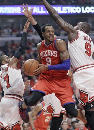 Philadelphia 76ers forward Andre Iguodala (9) looks to pass between Chicago Bulls guard C.J. Watson (7) and forward Luol Deng (9) during the first quarter of of Game 2 in an NBA basketball first-round playoff series, in Chicago on Tuesday, May 1, 2012. (AP Photo/Nam Y. Huh)