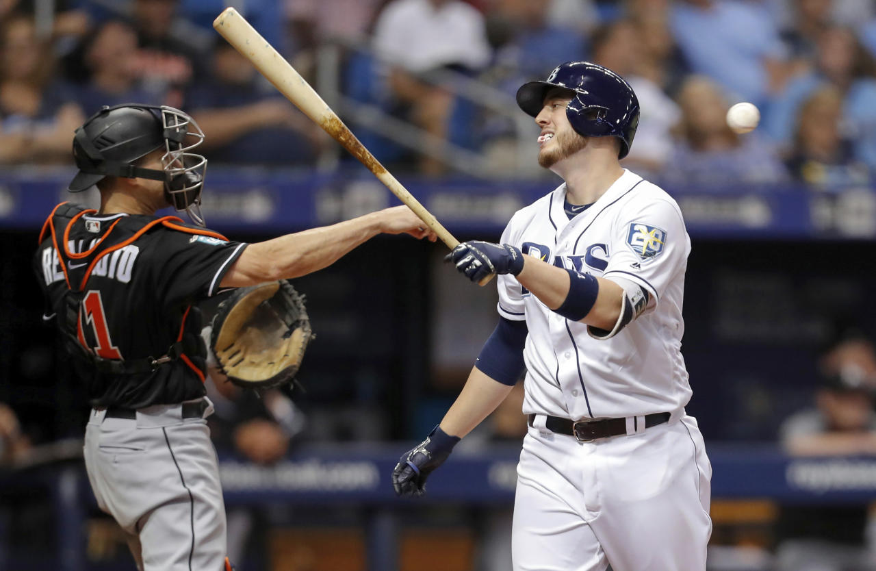 Tampa Bay Rays' C.J. Cron, right, reacts after striking out in front of Miami Marlins catcher J.T. Realmuto during the ninth inning of a baseball game Saturday, July 21, 2018, in St. Petersburg, Fla. (AP Photo/Mike Carlson)