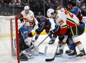 Colorado Avalanche goaltender Pavel Francouz, left, looks to stop a shot off the stick of Calgary Flames center Dillon Dube, front right, as he jostles in front of the net with Colorado defenseman Ryan Graves in the second period of an NHL hockey game Monday, Dec. 9, 2019, in Denver. (AP Photo/David Zalubowski)