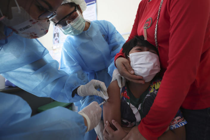 A young boy reacts as he receives a shot of the Sinovac's COVID-19 vaccine at a Samrong Krom health center outside Phnom Penh, Cambodia, Friday, Sept. 17, 2021. Prime Minister Hun Sen announced the start of a nationwide campaign to give COVID-19 vaccinations to children between the ages of 6 and 11 so they can return to school safely after a long absence due to measures taken against the spread of the coronavirus. (AP Photo/Heng Sinith)