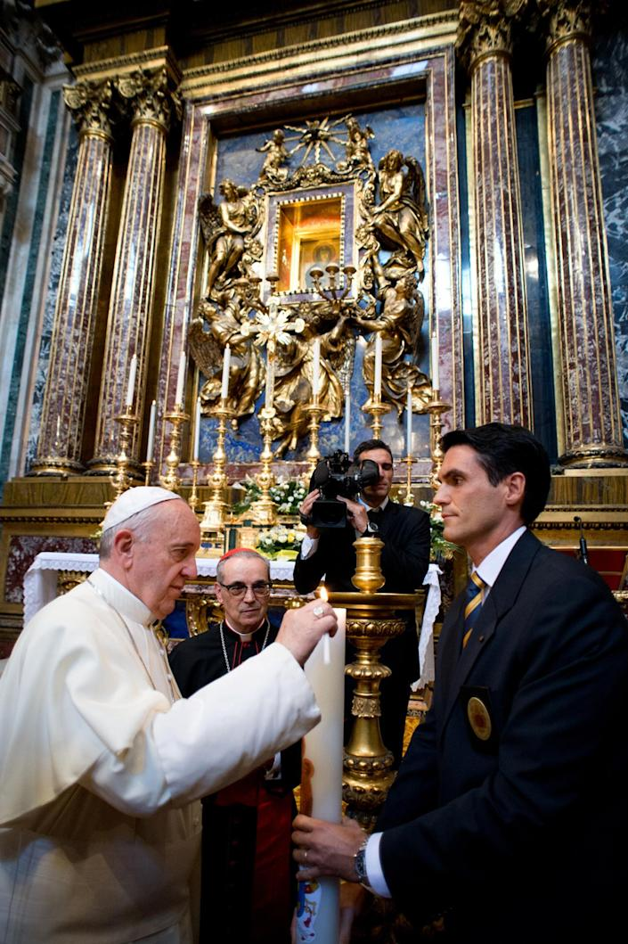 In this photo provided by the Vatican newspaper L'Osservatore Romano, Pope Francis lights a candle in Rome's St. Mary Major Basilica he unexpectedly visited for a moment of prayer in view of his upcoming trip to Brazil to celebrate the World Youth Day, Saturday, July 20, 2013. Francis leaves Monday, July 22 for Rio de Janeiro, where more than a million young Catholics are expected to celebrate their new pope. The 76-year-old Argentine became the church's first pontiff from the Americas in March, and the trip to Brazil is his first international journey since becoming pontiff. Catholic youth festivals are meant to reinvigorate the faithful, and Francis is expected to inspire young people with his humble ways. (AP Photo/L'Osservatore Romano, ho)