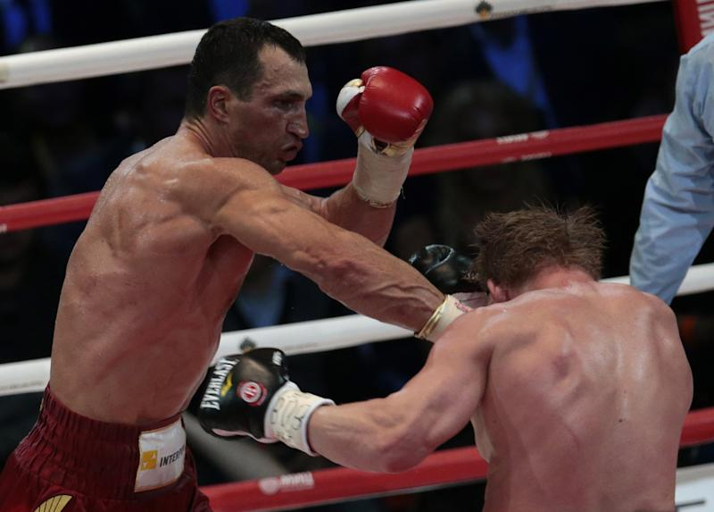Heavyweight champion Wladimir Klitschko, of Ukraine, left, hits Alexander Povetkin, of Russia, during their bout the Olympic Stadium, in Moscow, Russia, on Saturday, Oct. 5, 2013. Wladimir Klitschko successfully defended his WBA and IBF titles. (AP Photo/Ivan Sekretarev)