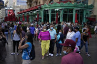 FILE - In this April 24, 2021, file photo, people walk along the Las Vegas Strip in Las Vegas. Masks are back in Las Vegas, where regional health officials pointed Friday, July 16, 2021, to a rising number of coronavirus cases and advised everyone, vaccinated or not, to wear facial coverings in crowded indoor places. (AP Photo/John Locher, File)