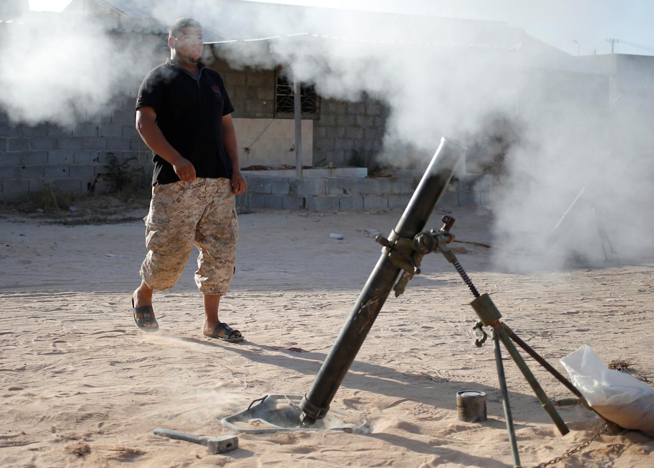 A fighter of Libyan forces allied with the U.N.-backed government fires a 81 mm mortar round in Sirte, Libya, July 26, 2016. REUTERS/Goran Tomasevic6