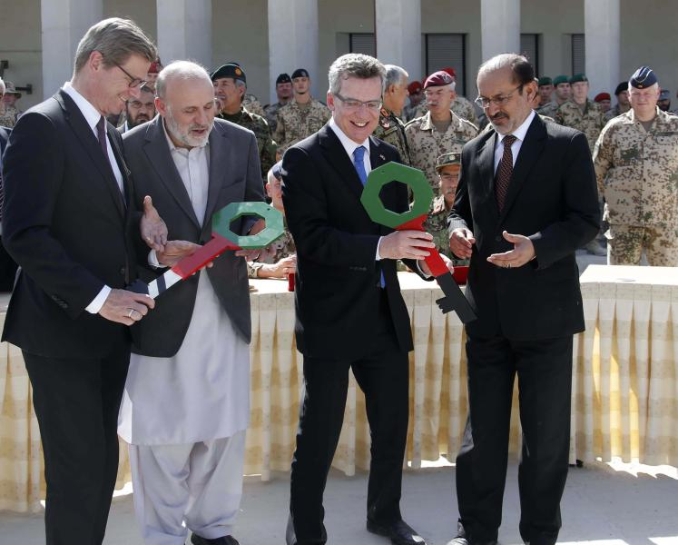Left to right: German Foreign Minister Guido Westerwelle, Afghan Interior Minister Mohammad Omar Daudzai, German Defense Minister Thomas de Maiziere and Afghanistan's Deputy Defense Minister Enayatullah Nazari exchange symbolic keys during the handover ceremony of a German base to Afghan armed forces in Kunduz, Afghanistan, Sunday, Oct. 6, 2013. Soldiers of the German contingency of the International Security Assistance Force, ISAF, withdrew from their base in Kunduz and the camp will be used by the Afghan National Army, ANA, and the Afghan National Civil Order Police, ANCOP. (AP Photo/Fabrizio Bensch, Pool)