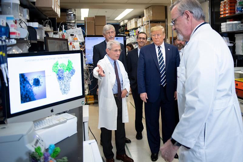 "National Institute of Allergy and Infectious Diseases Director Tony Fauci (L) speaks to US President Donald Trump during a tour of the National Institutes of Health's Vaccine Research Center March 3, 2020, in Bethesda, Maryland. - The US Federal Reserve announced an emergency rate cut responding to the growing economic risk posed by the coronavirus epidemic after the UN health agency said the world has entered ""uncharted territory"" with the outbreak's rapid spread. (Photo by Brendan Smialowski / AFP) (Photo by BRENDAN SMIALOWSKI/AFP via Getty Images)"