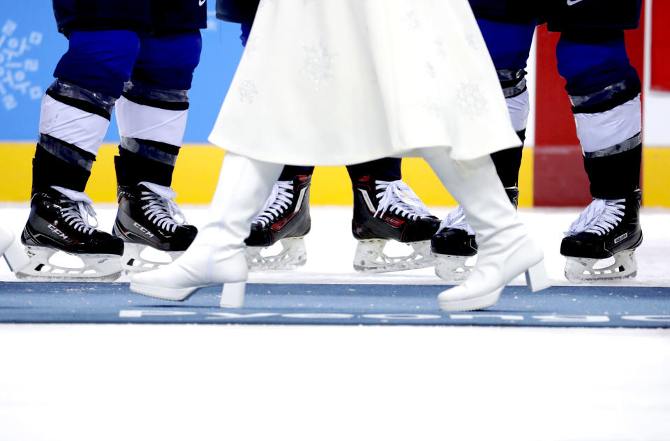 <p>A gift presenter walks by the United States players during the medals ceremony for Women's Hockey at the PyeongChang 2018 Winter Olympics in South Korea, Feb. 22, 2018.<br>(AP Photo/Julio Cortez) </p>