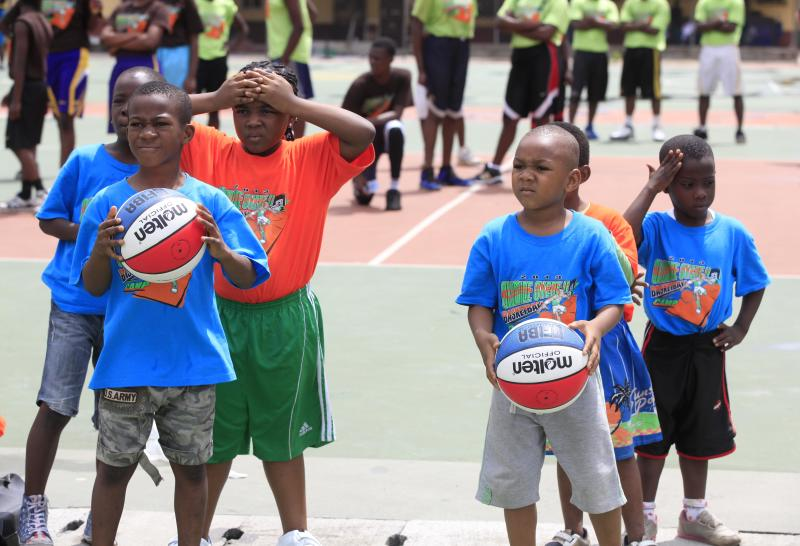 """In this photo taken Tuesday, Sept. 10, 2013, children exercise during a basket ball camp organized by former Seattle Supersonics and Orlando Magic center Olumide Oyedeji, in Lagos, Nigeria. About 30 years after NBA Hall of Famer Hakeem """"The Dream"""" Olajuwon first emerged from the sprawling city of Lagos, basketball is gaining momentum in this West African country of nearly 160 million people which, like most of the continent, has had little space for any sport other than soccer. (AP Photo/Sunday Alamba)"""