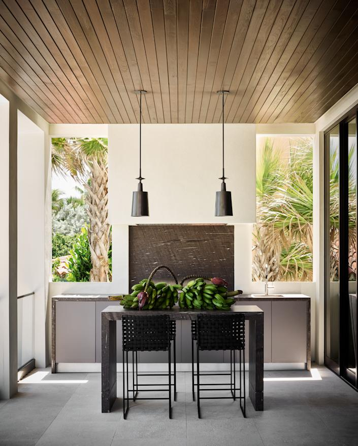 """<div class=""""caption""""> """"He said he wanted the coolest outdoor kitchen,"""" says Wecselman of Joyner. Her design allows him to cook at his <a href=""""https://caliberappliances.com/rockwell/"""" rel=""""nofollow noopener"""" target=""""_blank"""" data-ylk=""""slk:Rockwell by Caliber"""" class=""""link rapid-noclick-resp"""">Rockwell by Caliber</a> grill while enjoying his private beachfront views. Wecselman custom designed a table and paired it with counter stools by Mark Albrecht Studio, sourced from <a href=""""https://www.hollyhunt.com/"""" rel=""""nofollow noopener"""" target=""""_blank"""" data-ylk=""""slk:Holly Hunt"""" class=""""link rapid-noclick-resp"""">Holly Hunt</a>. </div>"""