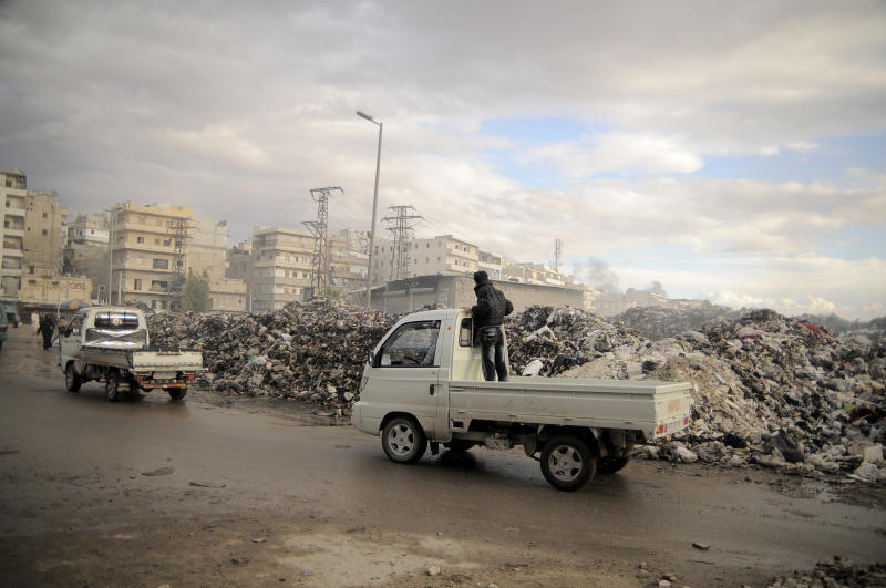 In this Saturday, Nov. 10, 2012 photo, trucks pass a mountain of garbage in a roundabout in Aleppo, Syria. Due the heavy fighting and shelling, the garbage collection system collapsed weeks ago. (AP Photo/Mónica G. Prieto)