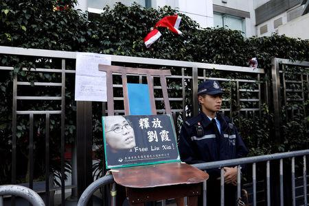 FILE PHOTO: A police officer stands guard next to a chair prop, alluding to an empty chair at late Liu Xiaobo's Nobel Peace Prize awarding ceremony in 2010, with an image of his wife Liu Xia, during a protest to urge for the release of Liu Xia, outside the Chinese liaison office in Hong Kong, China December 25, 2017. REUTERS/Tyrone Siu/File Photo