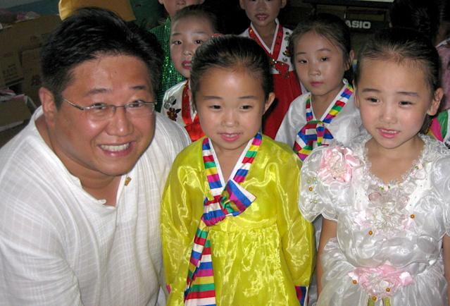 In this undated photo provided by the family of Kenneth Bae, Kenneth Bae, poses for a photoposes for a photo with a group of North Korean children. Bae, a 45-year-old tour operator and Christian missionary was arrested last November while leading a group of tourists in the northeastern region of Rason in North Korea and has been detained for the past 11 months. Bae's family said on Thursday, Oct. 10, 2013, that Bae's mother, Myunghee Bae, is being allowed to visit him. (AP Photo/Courtesy Terri Chung)