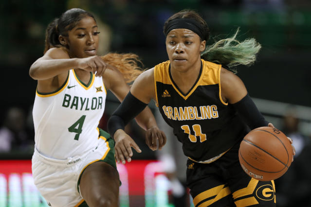 Grambling State guard Ariel Williams (11) advances the ball upcourt as Baylor guard Te'a Cooper (4) defends in the first half of an NCAA college basketball game in Waco, Texas, Friday, Nov. 8, 2019. (AP Photo/Tony Gutierrez)