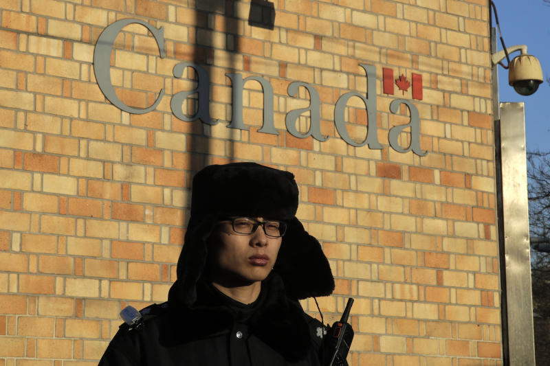 In this Wednesday, Dec. 12, 2018, file photo, a policeman stands watch outside the Canadian Embassy in Beijing. A Canadian court granted bail on Tuesday to a top Chinese executive arrested at the United States' request in a case that has set off a diplomatic furor among the three countries and complicated high-stakes U.S.-China trade talks. (AP Photo/Andy Wong, File)