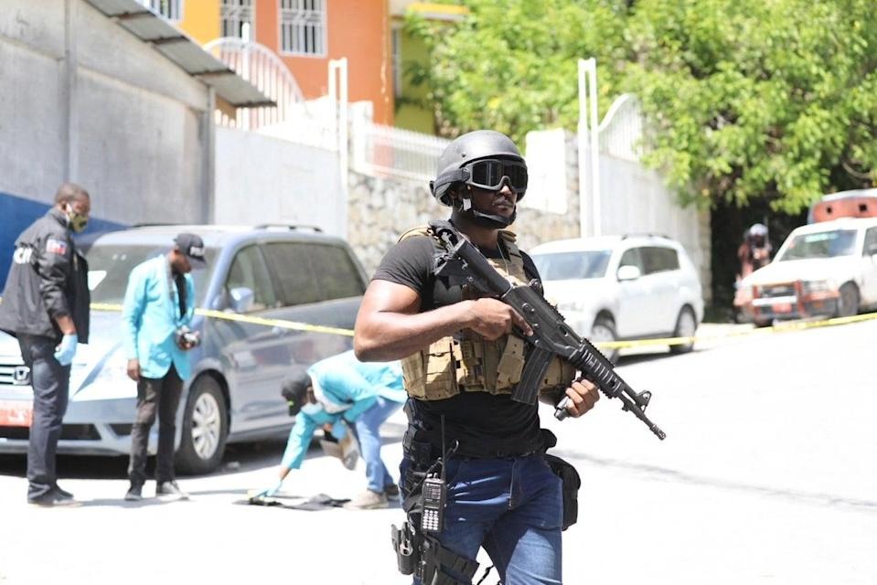 Members of the Haitian police and forensics look for evidence outside of the presidential residence. (AFP via Getty Images)