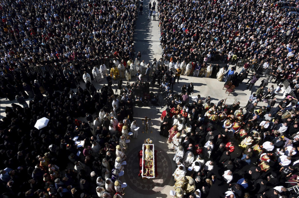 Thousands gathered by an open casket with Bishop Amfilohije's body during the liturgy and and funeral outside the main temple in the capital Podgorica, Montenegro, Sunday, Nov. 1, 2020. Bishop Amfilohije died on Friday after contracting the coronavirus weeks ago. A mass funeral on Sunday was held for the popular head of the Serbian Orthodox Church in Montenegro in violation of restrictions that are in place against the new coronavirus. (AP Photo/Risto Bozovic)