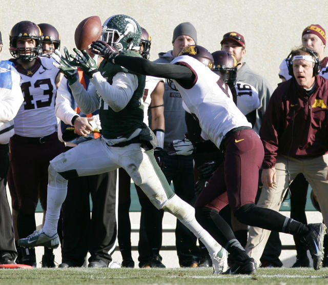 Michigan State's Darqueze Dennard, left, attempts to intercept a pass against Minnesota receiver Donovahn Jones during the third quarter of an NCAA college football game, Saturday, Nov. 30, 2013, in East Lansing, Mich. The ball fell incomplete. Michigan State won 14-3. (AP Photo/Al Goldis)