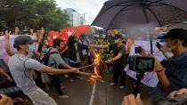Demonstrators burn a flag and a uniform during a protest in Yangon