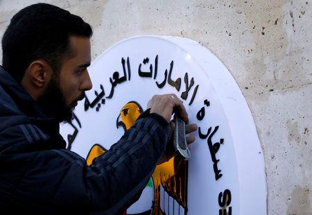 FILE PHOTO: A man works on the United Arab Emirates embassy emblem during its reopening in Damascus, Syria December 27, 2018. REUTERS/Omar Sanadiki/File Photo