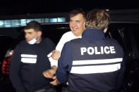 In this handout photo taken from video released by Georgian Interior Ministry Press Service, Georgian Police officers escort former President Mikheil Saakashvili after he was arrested in Rustavi, Georgia, Friday, Oct. 1, 2021. The prime minister of Georgia says former President Mikheil Saakashvili has been arrested. The announcement Friday by Prime Minister Irakli Garibashvili came about 18 hours after Saakashvili, who was convicted in absentia and has lived in Ukraine in recent years, posted on Facebook that he had returned to the country. (Georgian Interior Ministry Press Service via AP)