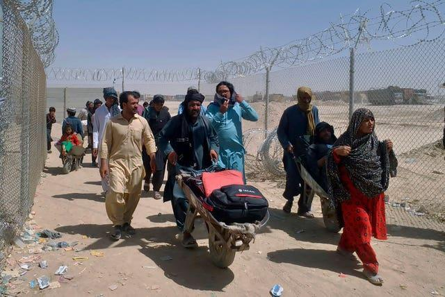 Afghan families enter Pakistan through a border crossing point in Chaman