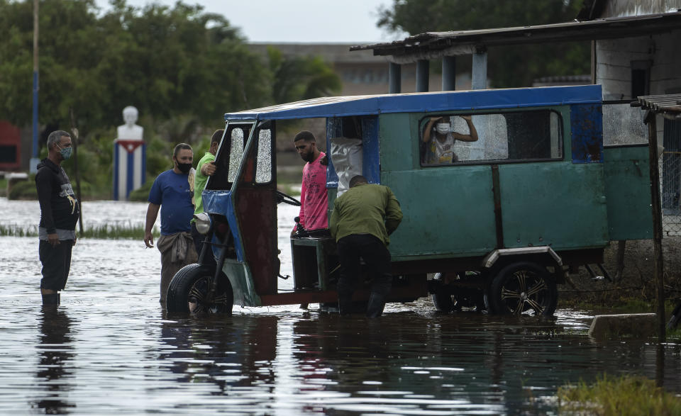 People try to start a stalled vehicle to transport people through a street flooded by rain brought on by Hurricane Ida, in Guanimar, Artemisa province, Cuba, Saturday Aug. 28, 2021. (AP Photo/Ramon Espinosa)