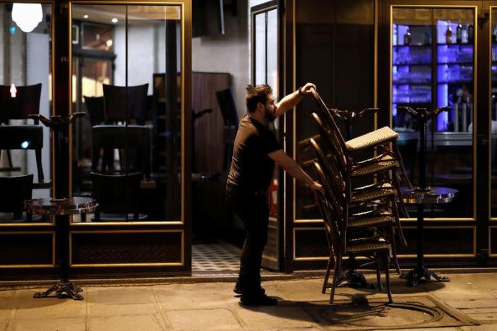 A bar employee clears out all the outside seats and prepares the closure of the place, as France's Prime Minister announced to close most all non-indispensable locations from midnight on Saturday, in Paris