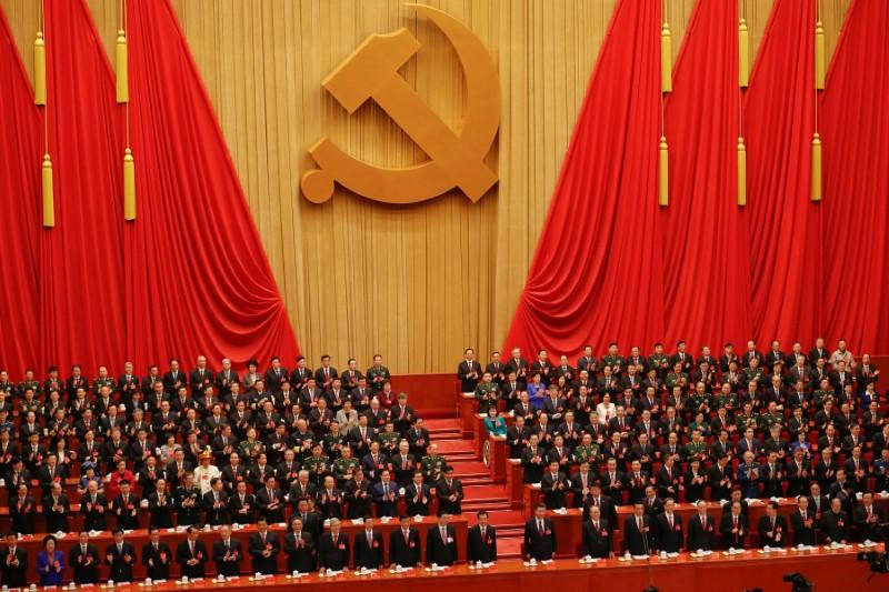 Chinese President Xi Jinping and other high ranking officials clap their hands during the opening session of the 19th National Congress of the Communist Party of China at the Great Hall of the People in Beijing