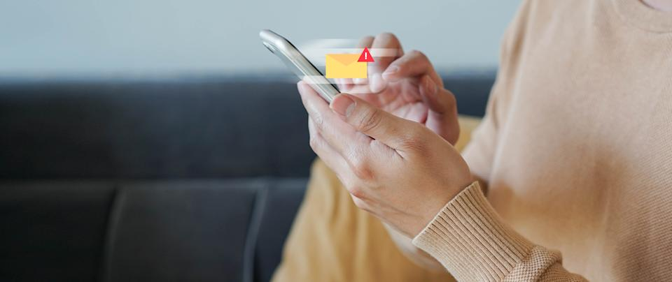 close up employee man hand holding smartphone to checking alert from mailbox with warning sign for email spam security and protection system technology concept
