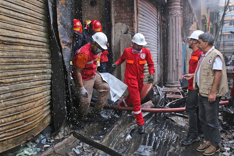 Firefighters retrieve a body from the site of a fire that broke out late Wednesday in closely set buildings in Dhaka, Bangladesh, Thursday, Feb. 21, 2019. (Photo: Rehman Asad/AP)
