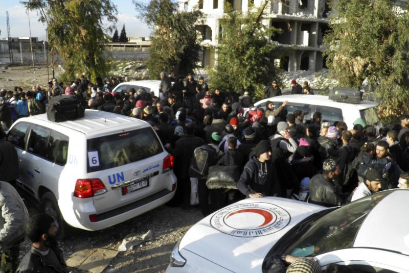 Civilians gather around vehicles as they wait to be evacuated from a besieged area of Homs