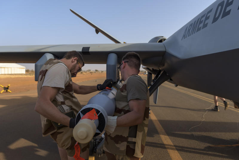 This photo provided by the French Defense Ministry communication center and taken Tuesday Dec. 17, 2019, shows French soldiers loading a French Reaper drone with a GBU 12 missile on Niamey airbase, Niger. France's defense ministry said Monday that it had carried out its first armed drone strike, killing seven Islamic extremists in central Mali over the weekend. France joins a tiny group of countries that use armed drones, including the United States. (Malaury Buis/EMA/DICOD via AP)