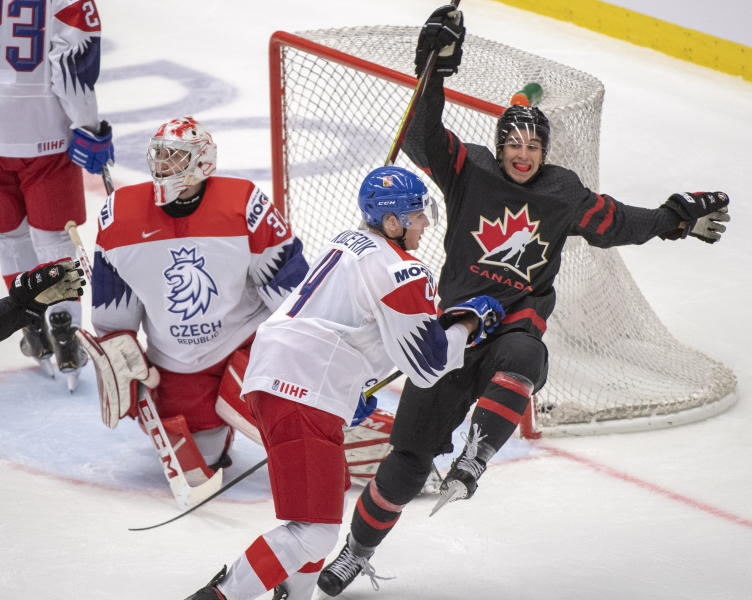Canada's Dylan Cozens, right, celebrates after scoring the sixth goal of the game for Canada against Czech Republic's goaltender Nick Malik as Czech's Radek Kucerik moves in during the second period at the World Junior Hockey Championships on Tuesday, Dec. 31, 2019 in Ostrava, Czech Republic. (Ryan Remiorz/The Canadian Press via AP)