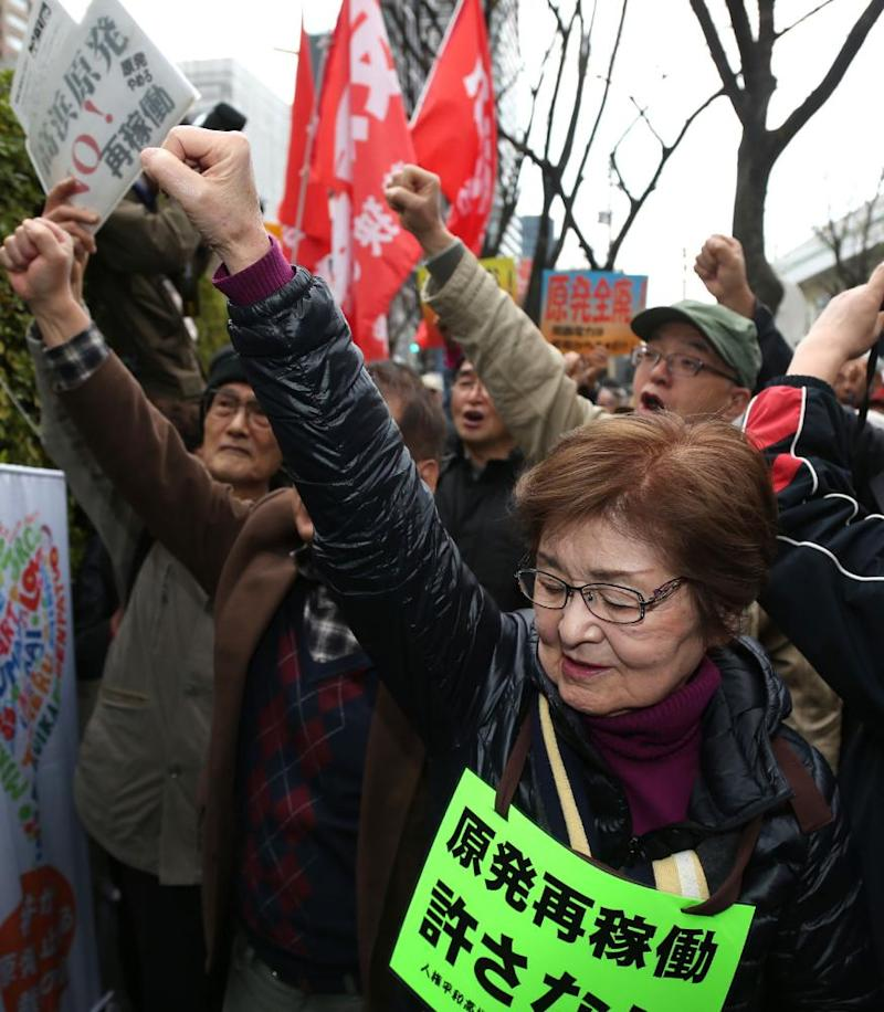 Anti-nuclear protesters stage a rally outside the Osaka high court.