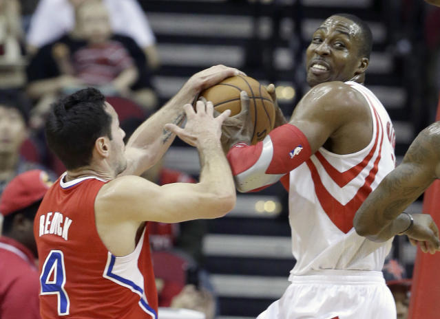 Los Angeles Clippers' J.J. Redick (4) and Houston Rockets' Dwight Howard, right, grapple for the ball in the first half of an NBA basketball game on Saturday, Nov. 9, 2013, in Houston. (AP Photo/Pat Sullivan)