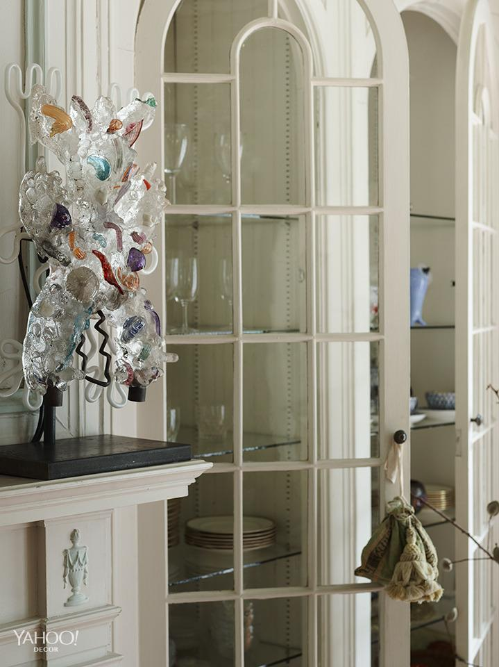 """<p>""""This is also the dining room — looking in the other direction. This glass piece is by a young artist named Chris Wolston. It functions as a wall sconce or standing lamp.""""</p>"""