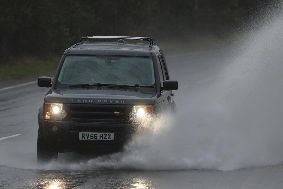 A car drives through a large puddle on the A20 in Folkestone, Kent. Parts of the UK are preparing to be lashed by heavy rain and high winds as Storm Alex heralds the arrival of a stretch of bad weather over the weekend.